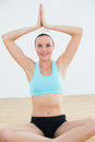 Smiling woman with joined hands over head at fitness studio portrait of a young Royalty Free Stock Images