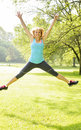 Smiling woman jumping in park happy female fitness instructor exercising outside at green Stock Photography
