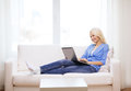 Smiling woman with laptop computer at home technology and internet concept sitting on the couch Stock Photo