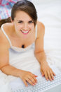 Smiling woman laying on bed and working on laptop Stock Photography