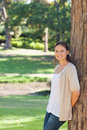 Smiling woman leaning against a tree Royalty Free Stock Photo