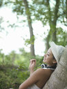 Smiling woman leaning on tree side view portrait of a young Royalty Free Stock Photos