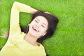 Smiling woman listening music and lying on a meadow Royalty Free Stock Photos