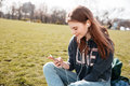 Smiling woman listening to musing from cell phone on lawn Royalty Free Stock Photo