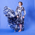 Smiling Woman with long flying dress on blue background Royalty Free Stock Photo