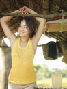 Smiling woman looking away in hut young mixed race with arms raised Stock Images