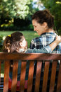 Smiling woman looking at daughter with arm around on wooden bench Royalty Free Stock Photo