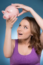 Smiling woman looking at piggy bank young for money in Royalty Free Stock Image