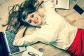 Smiling woman lying on back with laptop and smartphone Royalty Free Stock Photo