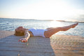 Smiling woman lying on pier attractive in white bathing suit wooden in nordic country during summer with legs raised in air Stock Photo