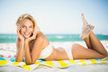 Smiling woman lying on a towel at the beach Royalty Free Stock Photo