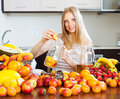 Smiling woman making fruits beverages at domestic kitchen Royalty Free Stock Image