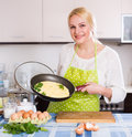 Smiling woman making  omlet Royalty Free Stock Photo