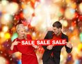 Smiling woman and man with red sale sign shopping gifts christmas couple x mas concept women men Stock Images