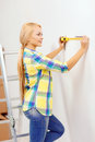 Smiling woman measuring wall repair building and home concept Royalty Free Stock Images