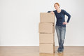 Smiling woman with moving or storage boxes full length photo of a young standing next to a stack of and Royalty Free Stock Images
