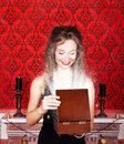 Smiling woman opening a christmas gift with rays in vintage room beautiful red Royalty Free Stock Photo