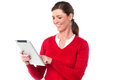 Smiling woman operating touch pad device lady placing her finger on the screen of Royalty Free Stock Image