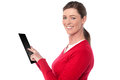 Smiling woman operating touch pad device lady placing her finger on the screen of Stock Image