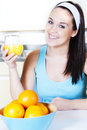 Smiling woman with orange juice in the kitchen dieting or healthy food concept Stock Image