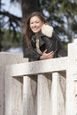 Smiling woman outdoor overlooking on marble balcony a beautiful girl is resting a she is dressed in a winter coat leather Royalty Free Stock Image