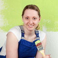 Smiling woman with paintbrush painting a wall a Stock Photo