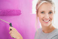Smiling woman painting her wall in pink and looking at camera Royalty Free Stock Photos