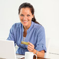 Smiling woman paying bills online banking home Stock Image