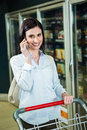 Smiling woman on phone in aisle Royalty Free Stock Photo