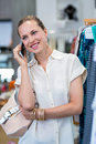 Smiling woman phoning next to clothes rail in clothing store Stock Images