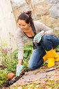 Smiling woman plant flowerbed hobby garden autumn