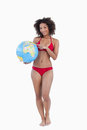 Smiling woman pointing a globe beach ball Stock Photography