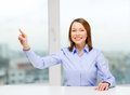 Smiling woman pointing to something imaginary business education and technology concept or pressing button Stock Photography