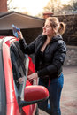 Smiling woman polishing car with rag portrait of Royalty Free Stock Photos