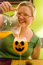 Smiling Woman Pouring Halloween Punch Stock Photography