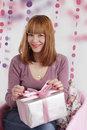 Smiling woman with present in pink decoration Royalty Free Stock Photo