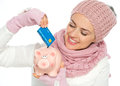 Smiling woman putting credit card in piggy bank Royalty Free Stock Photography