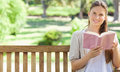 Smiling woman reading a book on a park bench Royalty Free Stock Photo