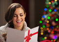 Smiling woman reading postcard in front of christmas tree young lights Stock Image