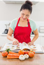 Smiling woman with recipe book and vegetables in kitchen young the at home Stock Photos
