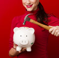 Smiling woman in red holds hammer above piggy bank savings a readies to break open her Stock Photo