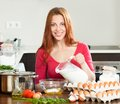 Smiling woman in red making dough or omlet in kitchen girl cooking omelet with milk home Royalty Free Stock Photo