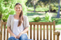 Smiling woman relaxing in the park on a bench Stock Images