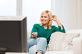 Smiling woman with remote watching tv at home Royalty Free Stock Photo