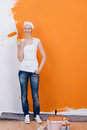 Smiling woman renovating painting her apartment with orange color Royalty Free Stock Image