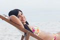 Smiling woman resting on deck chair beach Stock Photography