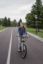 Smiling woman riding bicycle on asphalt road Royalty Free Stock Photo