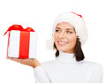 Smiling woman in santa helper hat with gift box christmas x mas winter happiness concept Royalty Free Stock Images