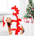 Smiling woman in santa helper hat with gift boxes christmas x mas winter happiness concept many Stock Photography