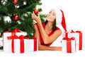Smiling woman in santa helper hat with gift boxes christmas x mas winter happiness concept many and tree Royalty Free Stock Photo